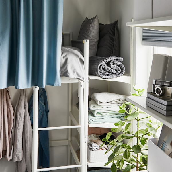 ALGOT white storage shelves are mounted on the wall by the foot end of a loft bed and store bed textiles and more.