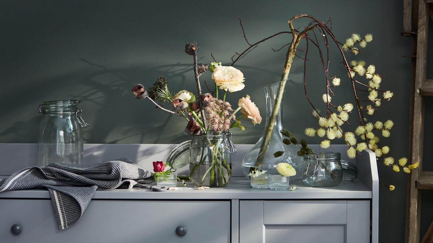 الجزء العلوي من خزانة جانبية HAUGAرمادي مملوء بمجموعة متنوعة من المزهريات والزهور، تتضمنإبريق زجاجي STORSINT.