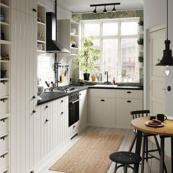 Alkoss egy kis konyhát vagy teakonyhát az IKEA METOD HITTARP fehér szekrényajtókkal és TORNVIKEN törtfehér nyitott tárolópolcokkal.