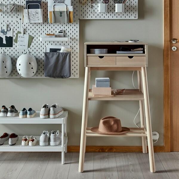 Álló íróasztal, fehér cipős polc és fali lyukacsos falitábla, sisakokkal.