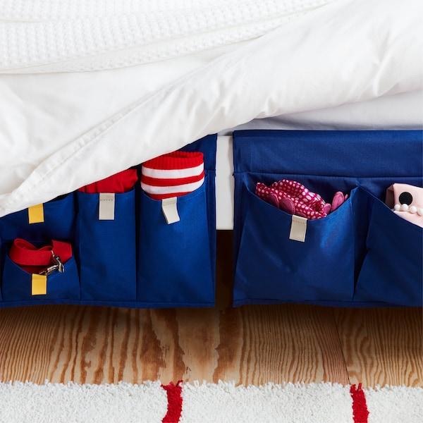 Almacenaje textil con bolsillos MÖJLIGHET en azul para guardar cosas a mano en un lateral de la cama.