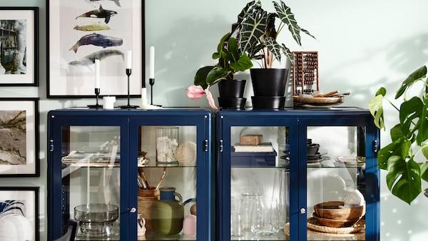 Almacenaxe nunha sala de estar con armarios con portas de vidro FABRIKÖR en azul.