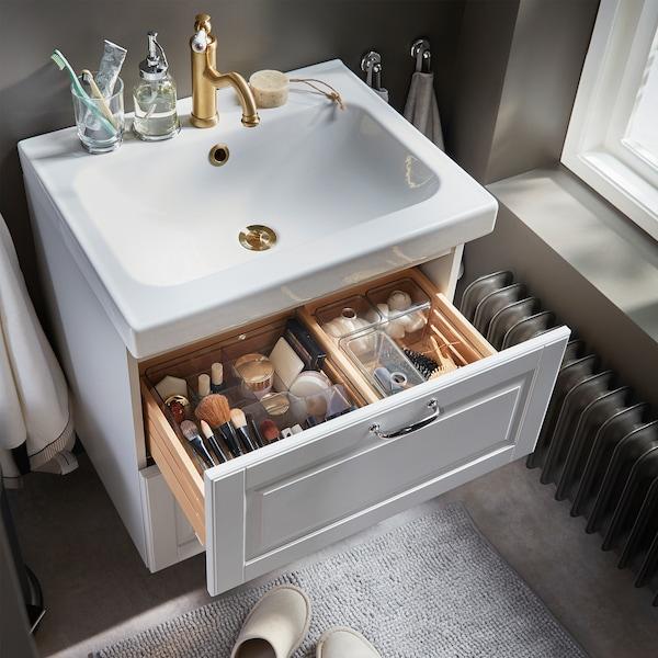 الماكياج وأدوات الشعر وأدوات التجميل منظّمة بشكل جيد في صناديق شفافة بلون داكن في درج وحدة حوض غسل.