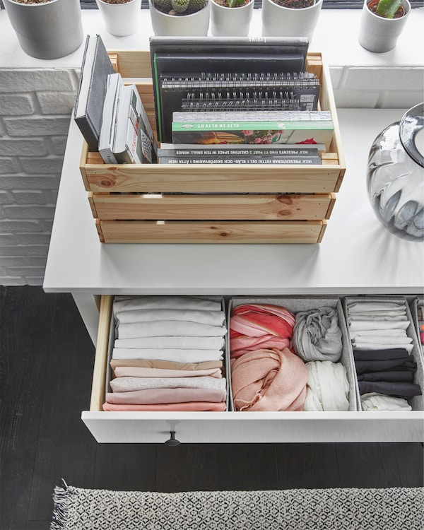 Almari 3 laci HEMNES berwarna putih dengan satu laci terbuka menunjukkan pakaian yang dilipat teratur dengan elok di dalam kotak.
