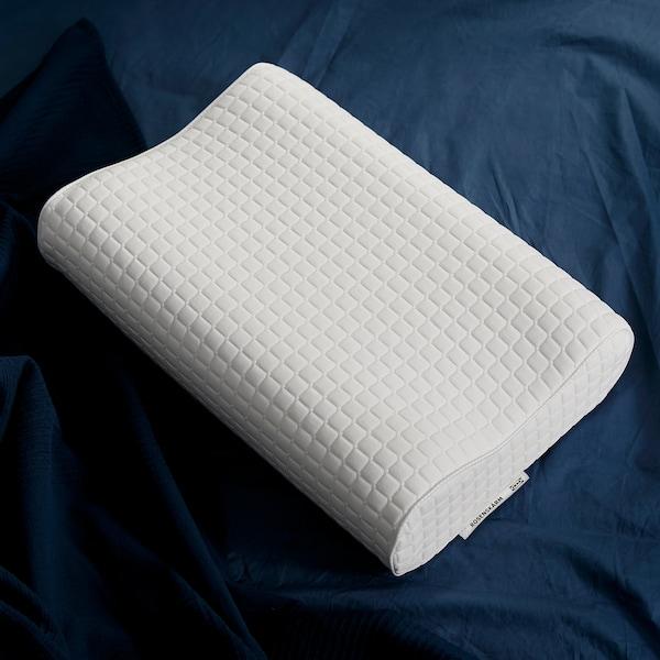 المخدة المريحة ROSENSKÄRM شكل التمبور من ايكيا، معروضة على مفارش سرير باللون الأزرق الداكن.