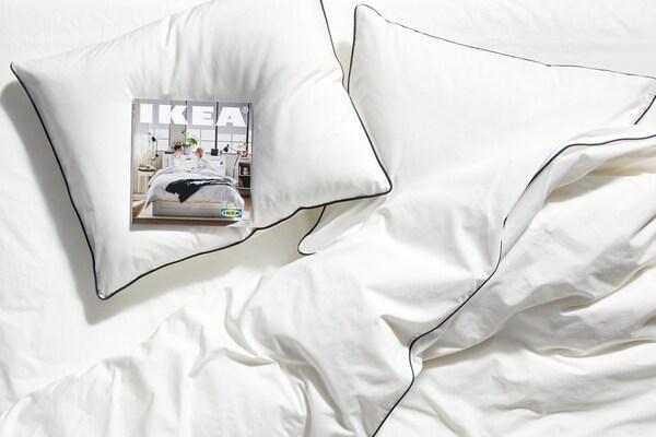 Almofadas brancas sobre uma cama com roupa de cama em branco e um exemplar do Catálogo IKEA 2020 pousado numa das almofadas.