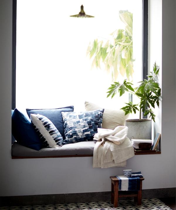 Almofadas e uma planta num assento à janela.