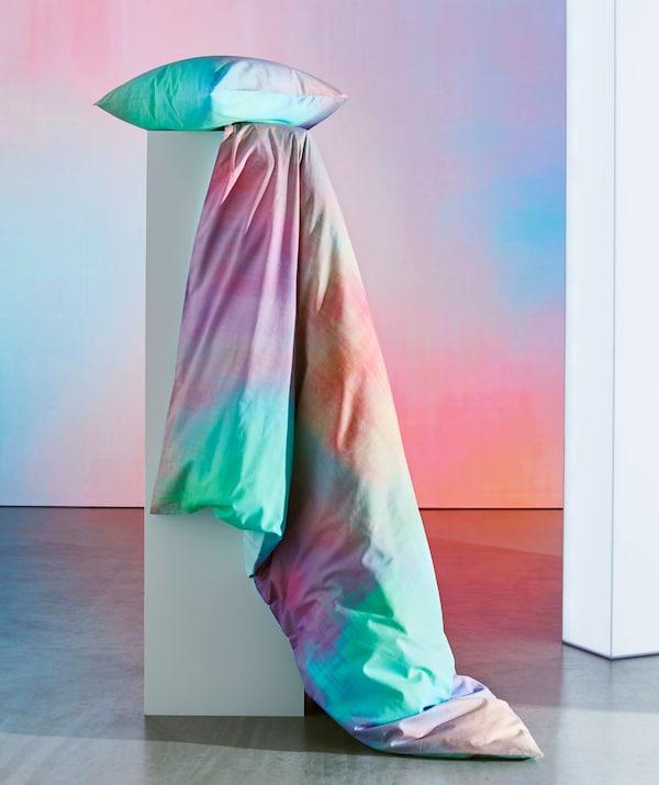 Almohada y colcha multicolor colocadas en una base.