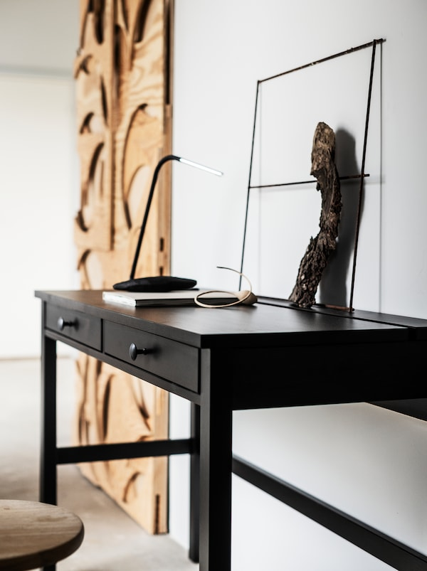 Along a wall in a white room stands a slimline, black HEMNES desk and a big, artful wall decoration in untreated wood.