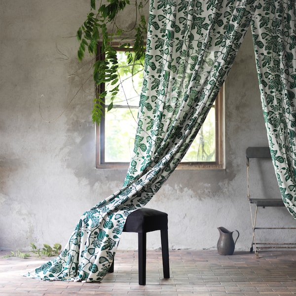 ALPKLÖVER curtains featuring a winding pattern of fig leaves in white and green is draped over a black foot stool.