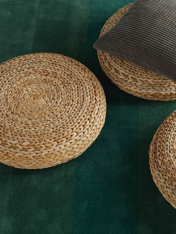 ALSEDA rattan stools placed over green carpet. A cushion over a rattan stool.