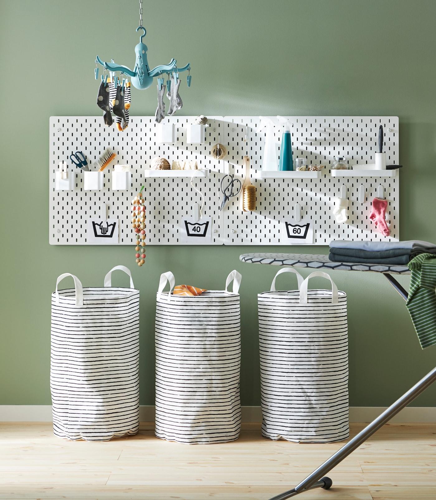 Alt til klesvasken oppbevart på hyller, i potter og på knagger på ei hvit tavle.