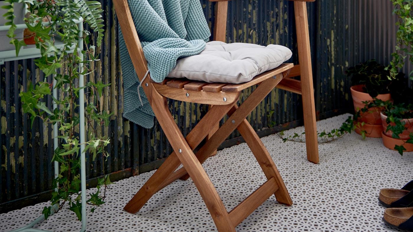 ALTAPPEN vlonders bedekken de vloer van een balkon met een ASKHOLMEN opklapbare stoel en tafel en planten.
