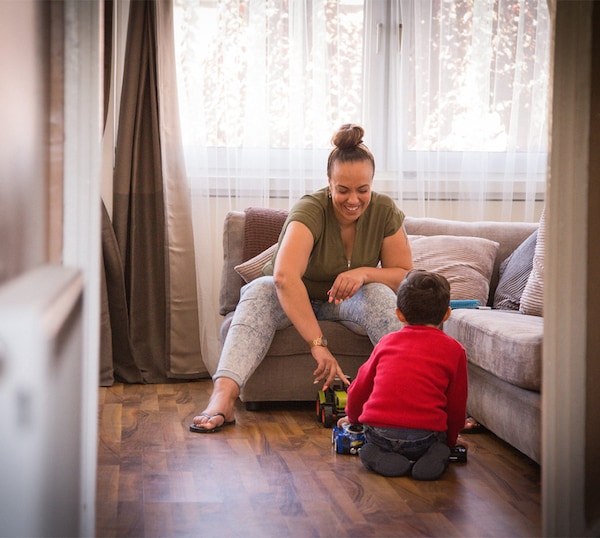 أم وابنها الصغير يجلسان في غرفة الجلوسويلعبان معًا بشاحنة لعبة.