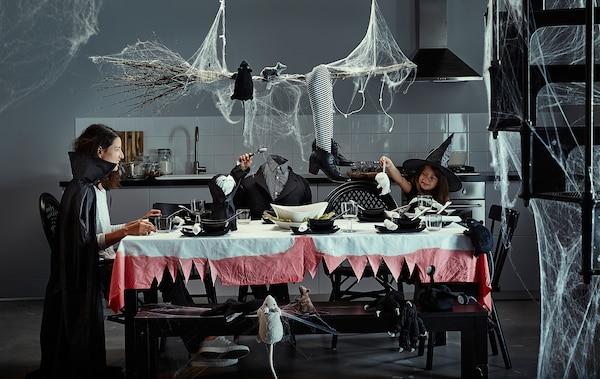 Ama eta bi seme-alabak Halloweenerako apainduta dagoen jangelako mahian eserita.