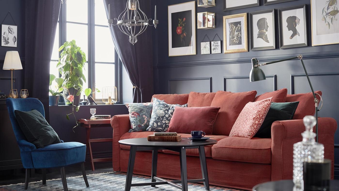 Ambiente dallo stile tradizionale con pareti rivestite da pannelli scuri, immagini incorniciate, divano GRÖNLID rosso con cuscini e tavolino KRAGSTA.