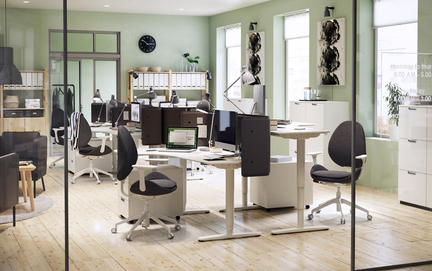 Ambiente de trabalho com uma decoração moderna, com paredes em verde claro e secretárias de canto BEKANT, reguláveis, em branco.