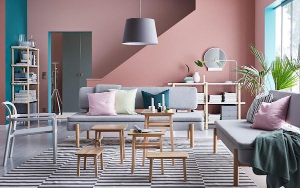 Aménagez un salon contemporain avec le canapé convertible YPPERLIG en Orrsta gris clairet la série de tables gigognes YPPPERLIG en hêtre devant un mur vieux rose.