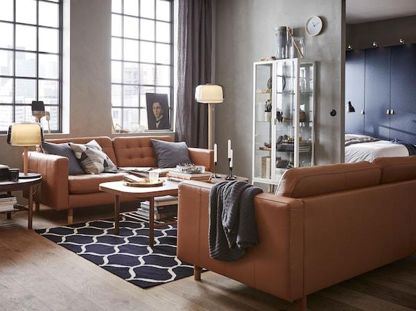 Aménagez un séjour moderne et aéré avec la vitrine MILSBO, les canapés sobres LANDSKRONA en cuir brun et les tables basses LISTERBY en bois foncé.