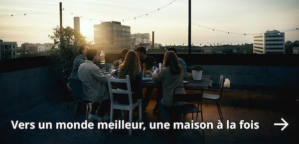 Amis réunis autour d'une table sur un toit au coucher de soleil.