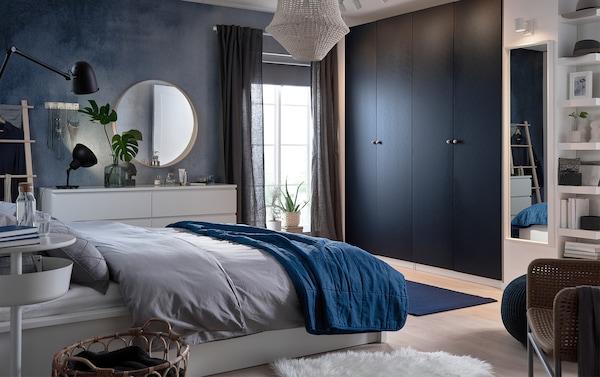امنح غرفة نومك جوًا من الهدوء والسكينة مع اللون الأزرق بمختلف درجاته من خلال أبواب خزانة الملابس الجديدة IKEA PAX HAMNÅS باللون الأزرق الداكن المطعّم بالأسود، ومقعد SANDARED باللون الأزرق الغامق، وسجاد STOCKHOLM حياكة مسطحة باللون الأزرق القاتم.