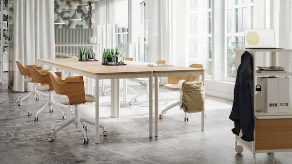 Ampia e luminosa sala riunioni, con tavoli e sedie in legno chiaro e bianco, tende bianche sottili e parete in vetro.