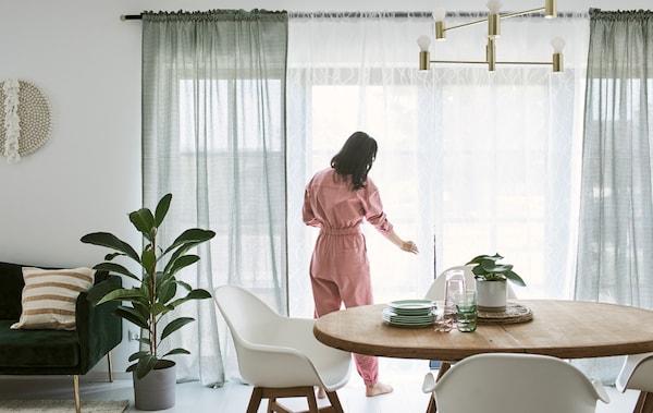 امرآةترتدي أوفرول وردي وتقومبتثيت الستائرعلى نافذة فرنسية في غرفة طعامبها طاولة طعاموكراسي بيضاء.