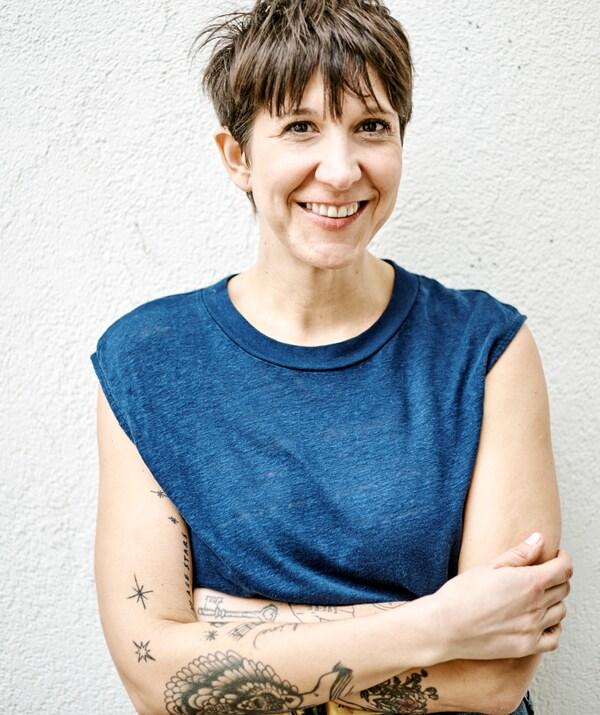 امرأة بقصة شعر أحمر قصير ووشم على الذراعين، ترتدي تي شيرت أزرق بدون أكمام وتقف بمحاذاة حائط أبيض.