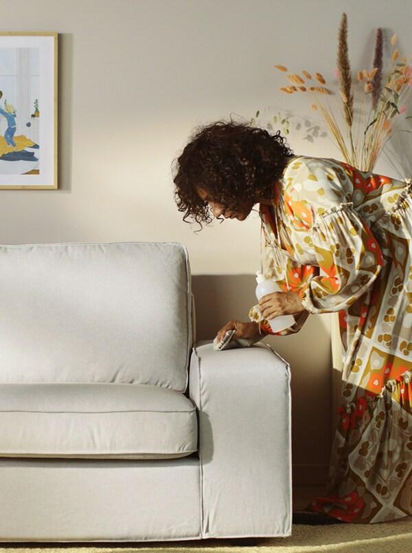امرأة في غرفة مشمسة وفي يدها زجاجةسائل تنظيف وقطعة قماش في الأخرى تقومبمسح ذراع صوفا رمادية.
