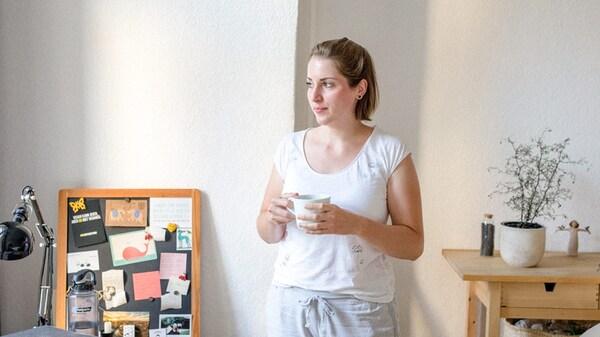 امرأة شابة في منزلها، تحمل كوب شاي وتنظر خارج النافذة.