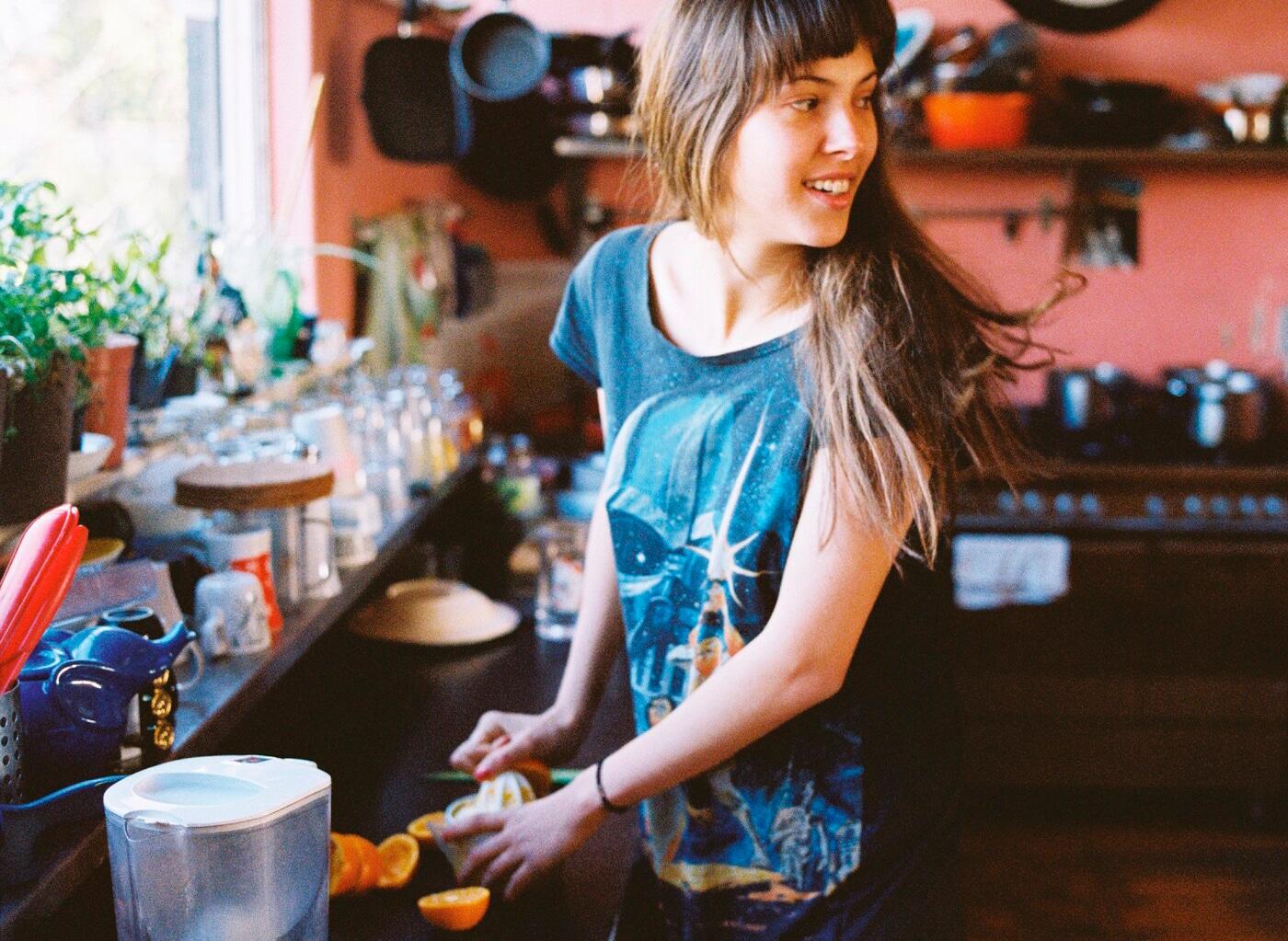 امرأة شابة تستدير للنظر نحو شخص بينما تقوم بغسل وتقطيع الفاكهة في حوض المطبخ.