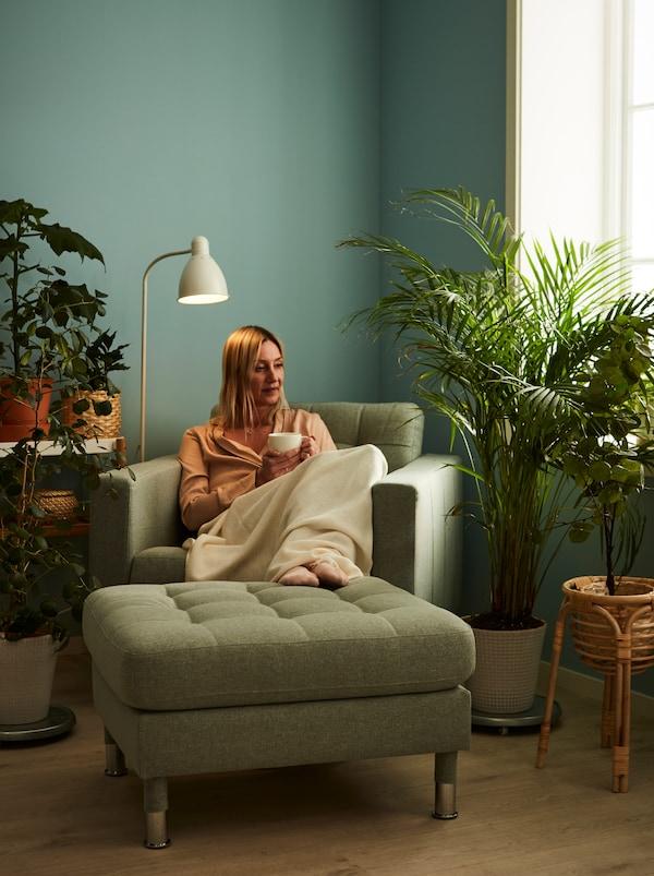 امرأة تجلس على كرسي بذراعين LANDKRONA، وفي يدها كوب شاي ومحاطة بالنباتات، بعضها على حامل نباتات BUSKBO.