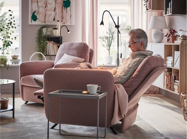 امرأة تجلس بشكل مريح على كرسي بظهر متحرك EKOLSUND مع GUNNARED غطاء بني-وردي فاتح بجانب طاولة قهوة.