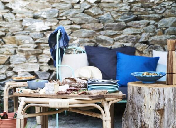 Amuse-gueule servis sur des planches à découper en bois posées sur une table basse, canapé garni de coussins bleus et adossé au mur de pierre.