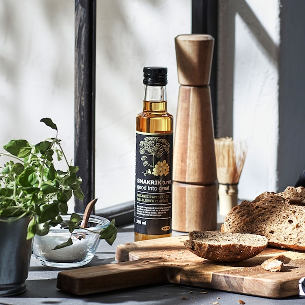 An acacia wood spice mill, shown with a bottle of gourmet oil and a cutting board heaped with slices of bread.