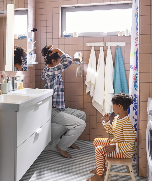 An adult and child in a bathroom with double sinks, a stool and two mirrors.