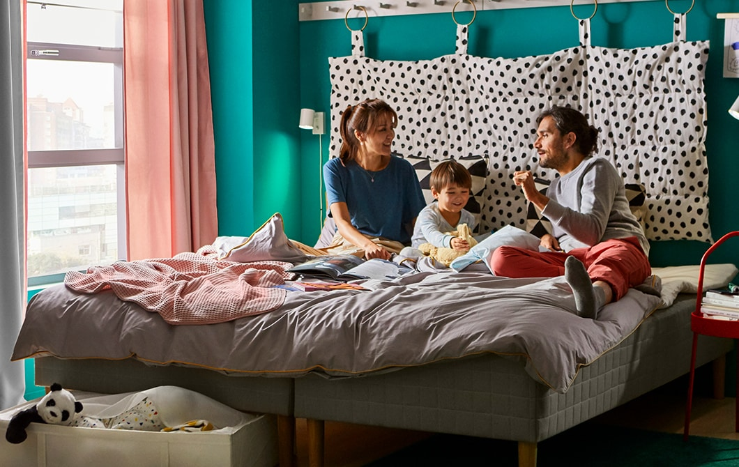 An adult and child playing on a double bed with underbed storage drawers, with curtains hanging around the bed and artwork on the walls.