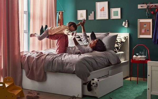 An adult and child playing on a queen bed with underbed storage drawers, with curtains hanging around the bed and artwork on the walls.