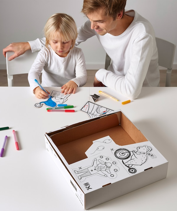 An adult sits with a child who is colouring in circus drawings, cut from the cardboard box on the table.