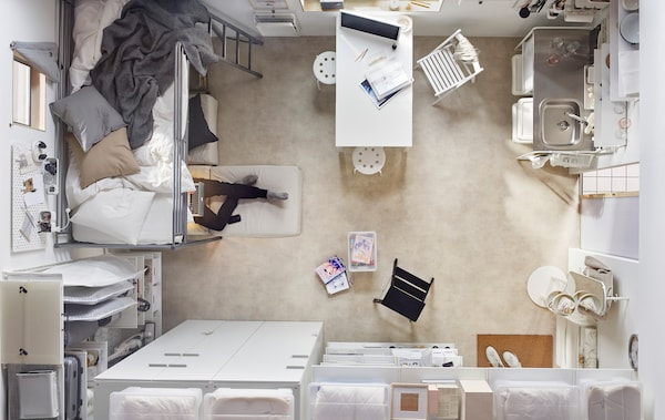 An aerial view of a compact living space, including a bed, wardrobes, dining table and small kitchen unit.