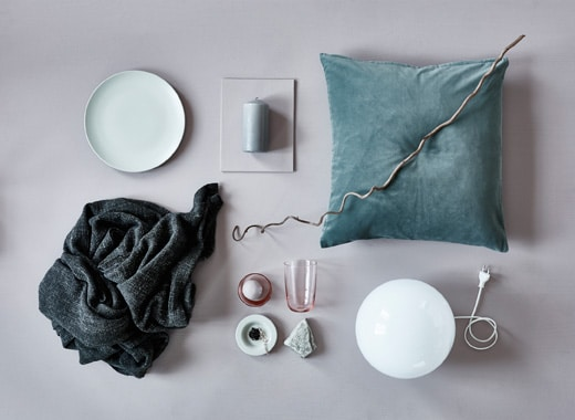 An aerial view of a cushion, blanket, a lamp and natural elements for fall decoration