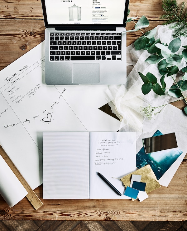 An aerial view of a desk with a computer, notebooks, a wedding planning timeline and fabric swatches