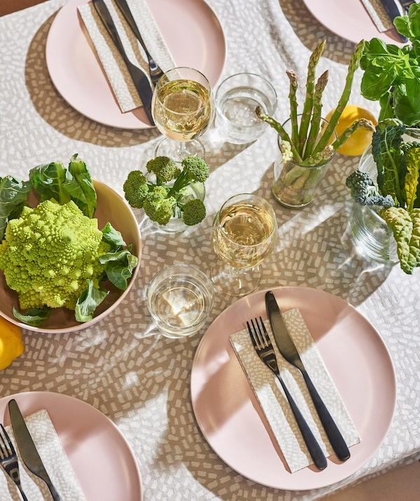 An aerial view of an outside dining table set with pink plates, cutlery, plants and vegetables presented in bowls.