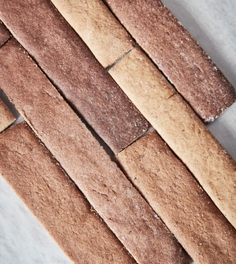 An aerial view of gingerbread cut into pieces to look like wooden floor planks.A small IKEA LACK table made from gingerbread. A small IKEA KOLDBY rug made from gingerbread