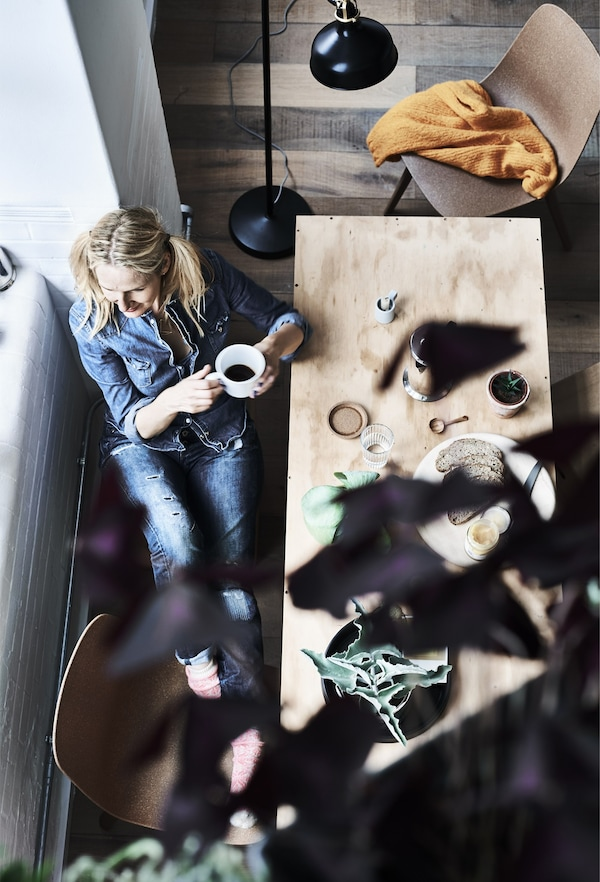 An aerial view of Jules drinking coffee at the dining table.