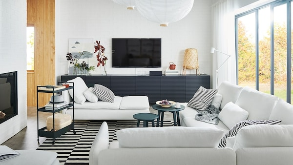 An airy living room with a large SÖDERHAMN sofa, a SÖDERHAMN chaise longue and BESTA storage with STOCKVIKEN doors.