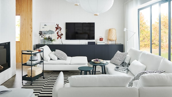 An airy living room with a large SÖDERHAMN sofa, a SÖDERHAMN chaise lounge and BESTA storage with STOCKVIKEN doors.