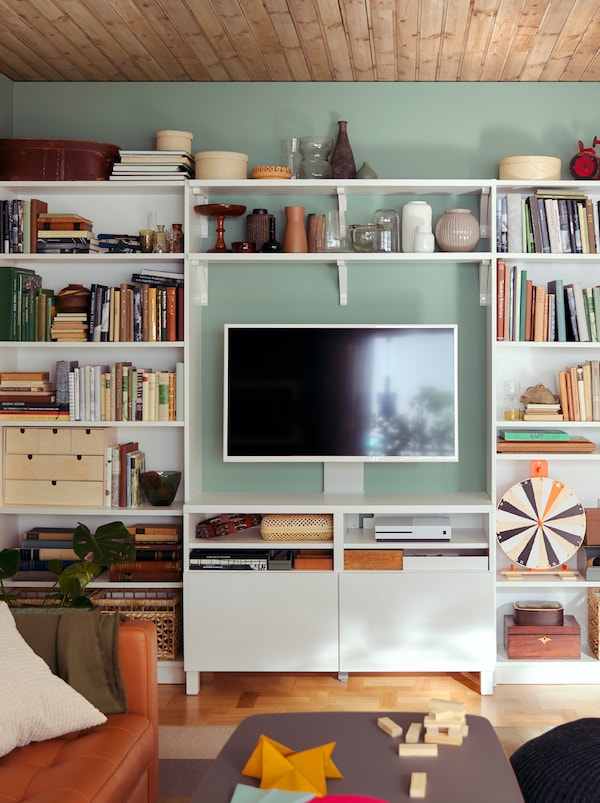 An all-inclusive, living-room storage wall formed by a combination of BILLY bookcases and BERGSHULT/SANDSHULT shelves.