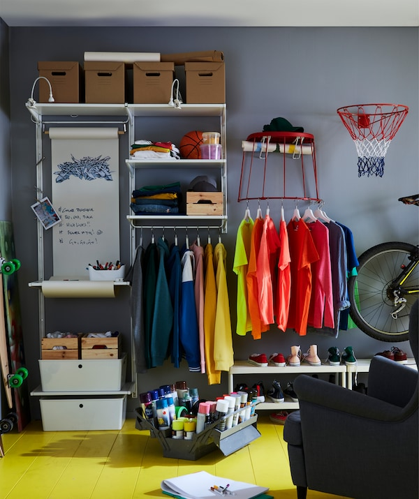 An angle of a room with the white, wall-mounted storage system ALGOT, filled with different kinds of things.