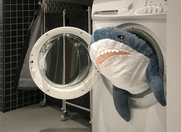 An angle of an IKEA store showing a washing machine with BLÅHAJ, a big soft toy resembling a shark sticking out of it.